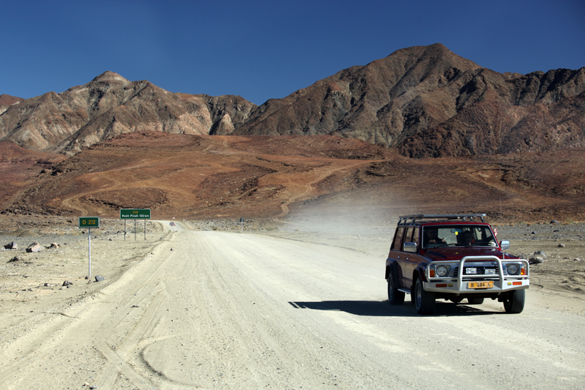 Namibie, Aussenkher, à proximité du Fish River Canyon,  un 4x4 roule sur une piste entourée de montagnes longeant la rivière Orange