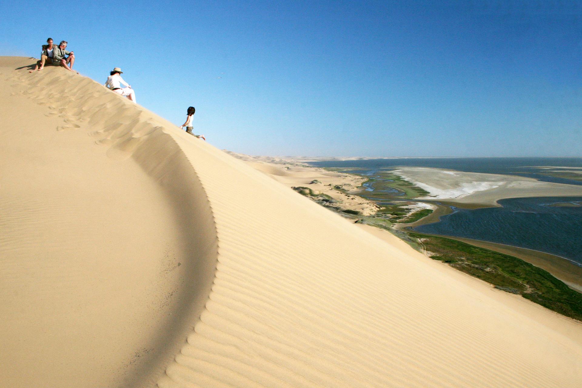 Namibie, une famille admire du haut d'une dune le panorama de lagunes de Sandwich Harbour