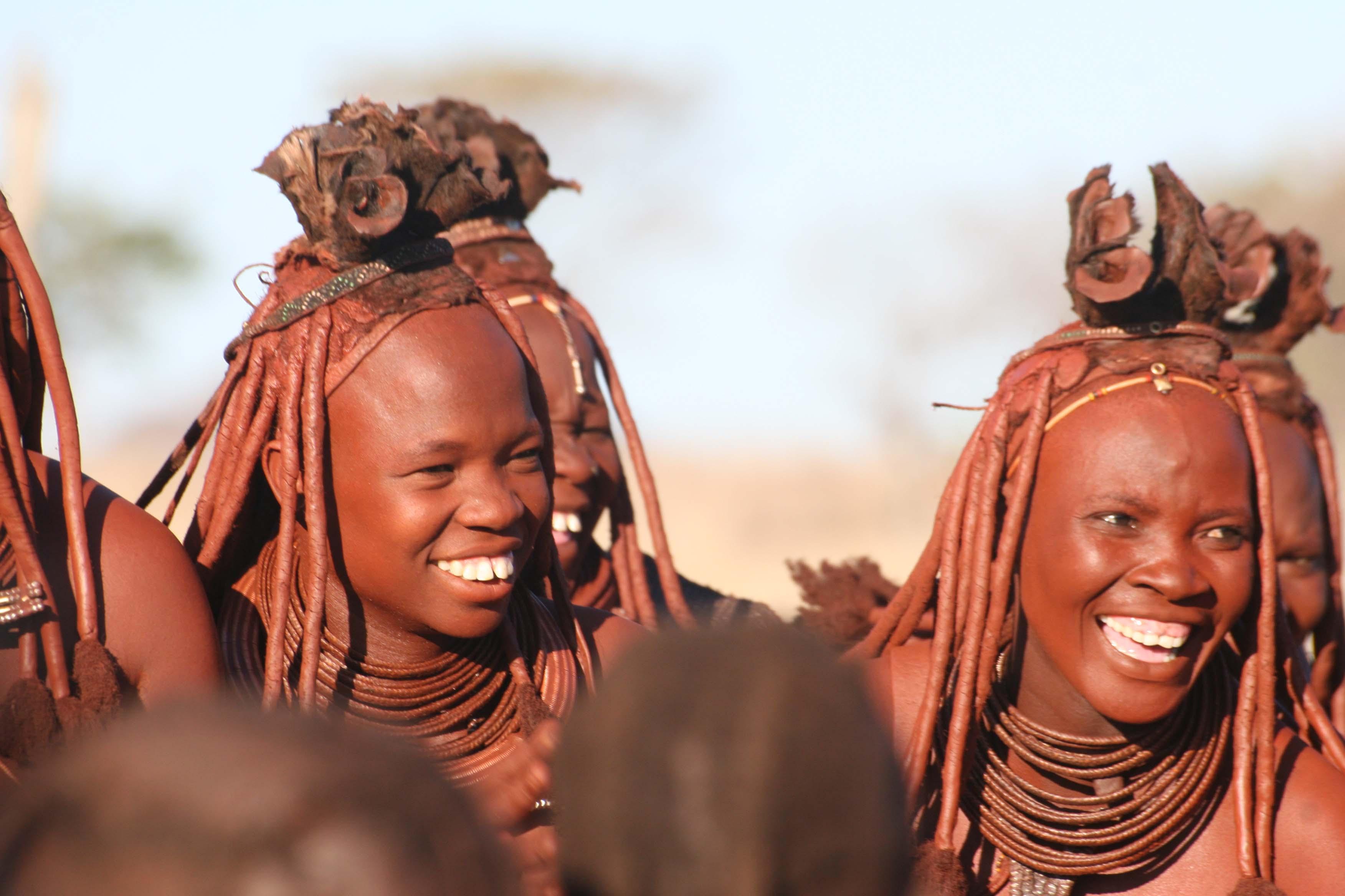 Namibie, Kaokoland, au milieu d'une danse, deux femmes Himba en tenue traditionnelle affichent de grands sourires
