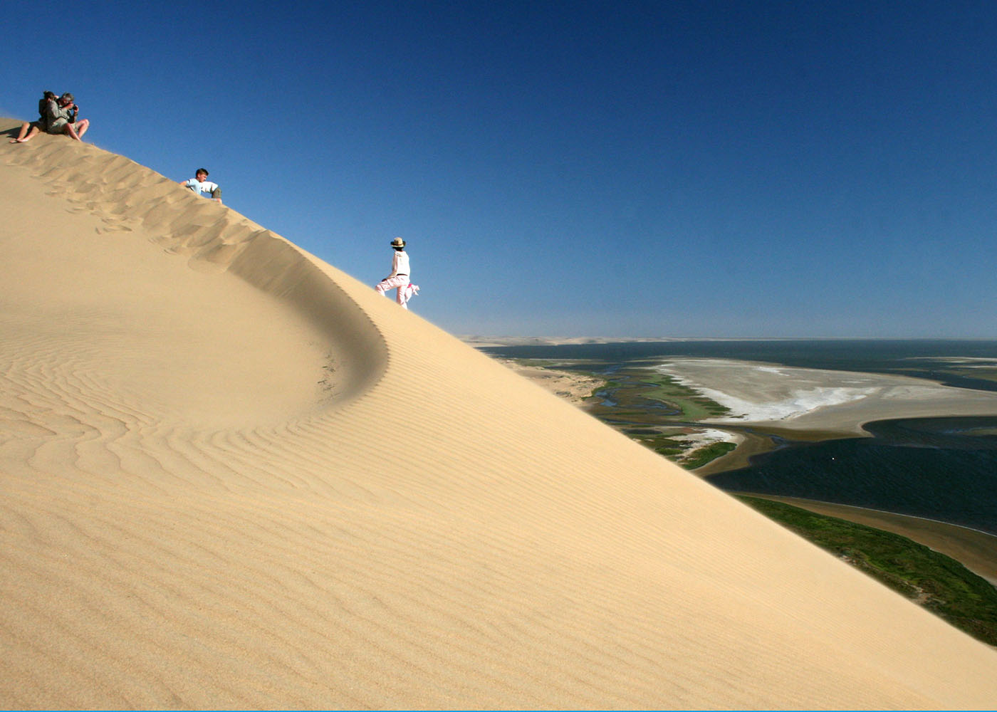 Namibie, au sud de Walvis Bay, une famille admire du haut d'une dune le panorama de lagunes de Sandwich Harbour