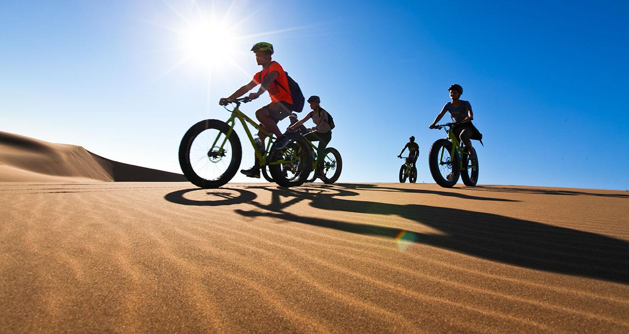 Namibie : une famille se promène avec leur fatbike dans les dunes près de Swakopmund