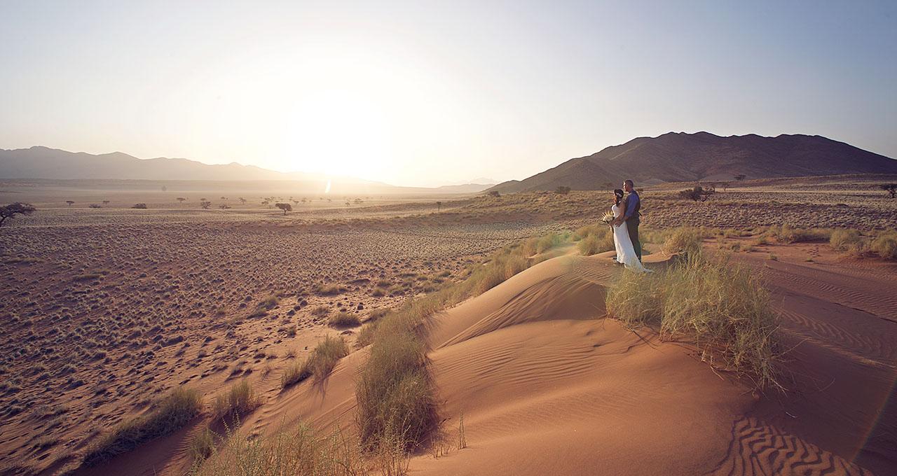 Namibie, Wolwedans, photo de charme d'un couple de mariés regardant le désert du haut d'une dune