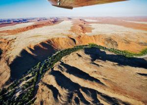 Namibie, vue aérienne du canyon de la rivière Kuiseb, limite de verdure entre les dune ocres au sud, et les plaines de graviers au nord du désert du Namib