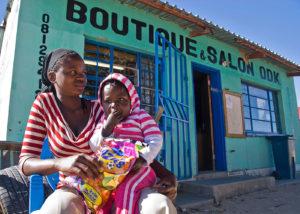 Namibie, Rundu, femme avec un enfant assise devant un magasin/salon de coiffure local