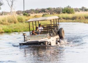 Botswana, 4x4 avec des occupants amusés traversant un gué profond dans le delta de l'Okavango
