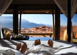 Namibie, Wolwedans Lodge, un couple profite du moment pour une grasse matinée passée au lit avec une vue exceptionnelle sur le NamibRand réserve