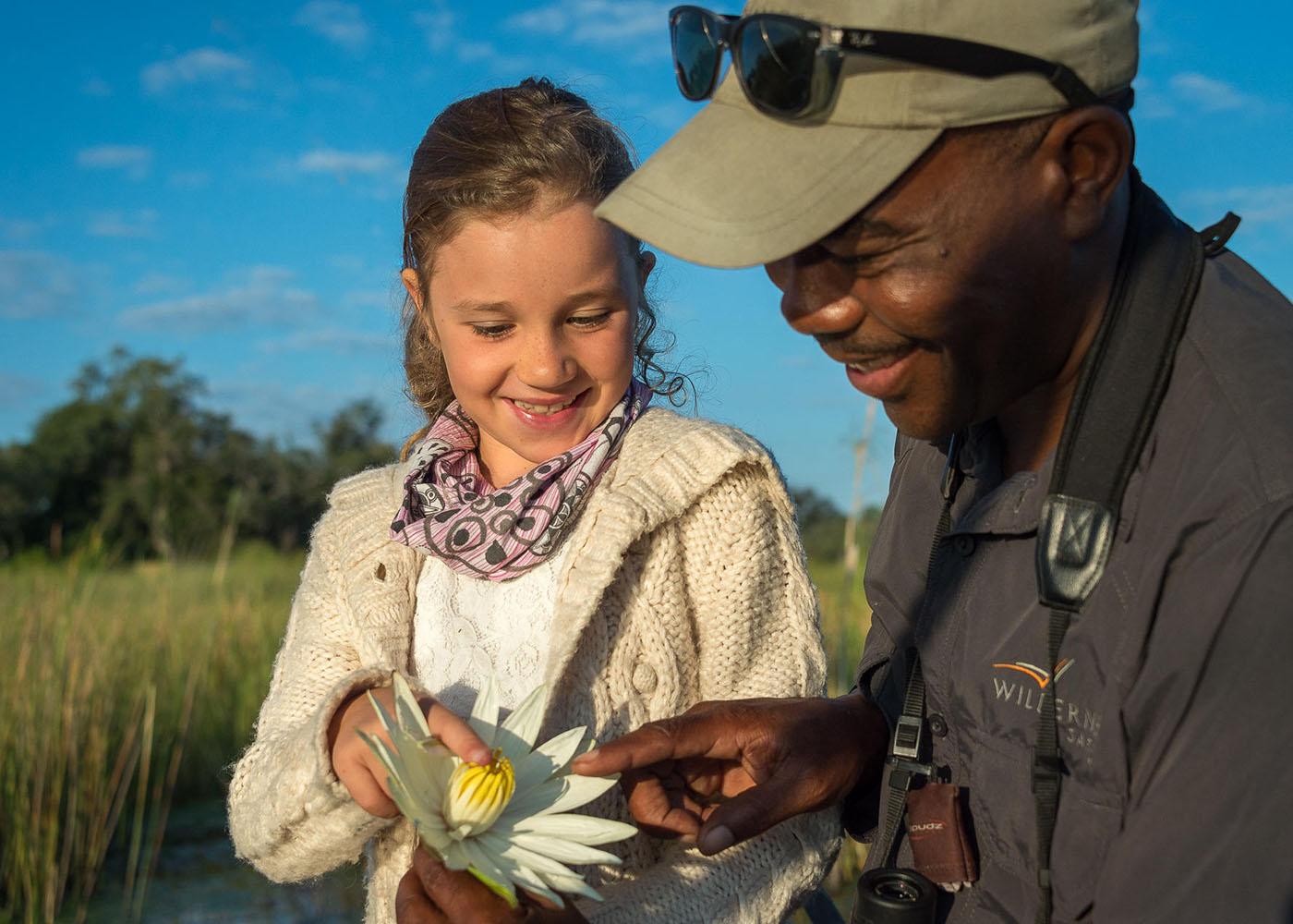 Botswana, en bateau dans le delta de l'Okavango, un guide montre un nénuphar à jeune fille
