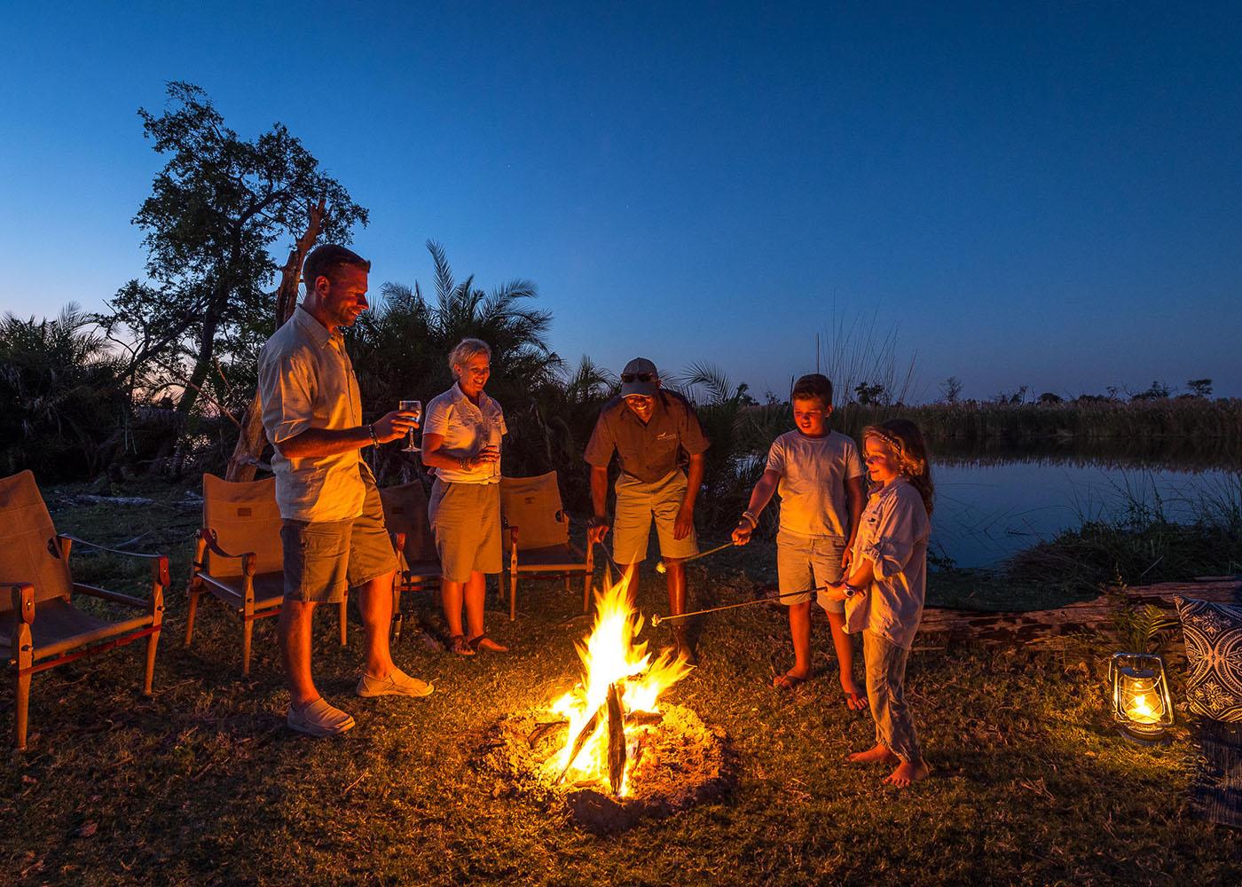 Botswana, une famille un verre à la main autour un feu, à proximité de la rivière dans le delta de l'Okavango