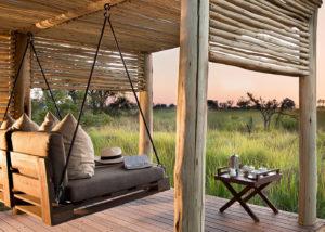 Botswana, ambiance de charme et de relaxation, fauteuil balançoire et station de café, vue donnant sur les étandues sauvages et verdoyantes du delta de l'Okavango au andBeyond Nxabega Okavango Tented Camp