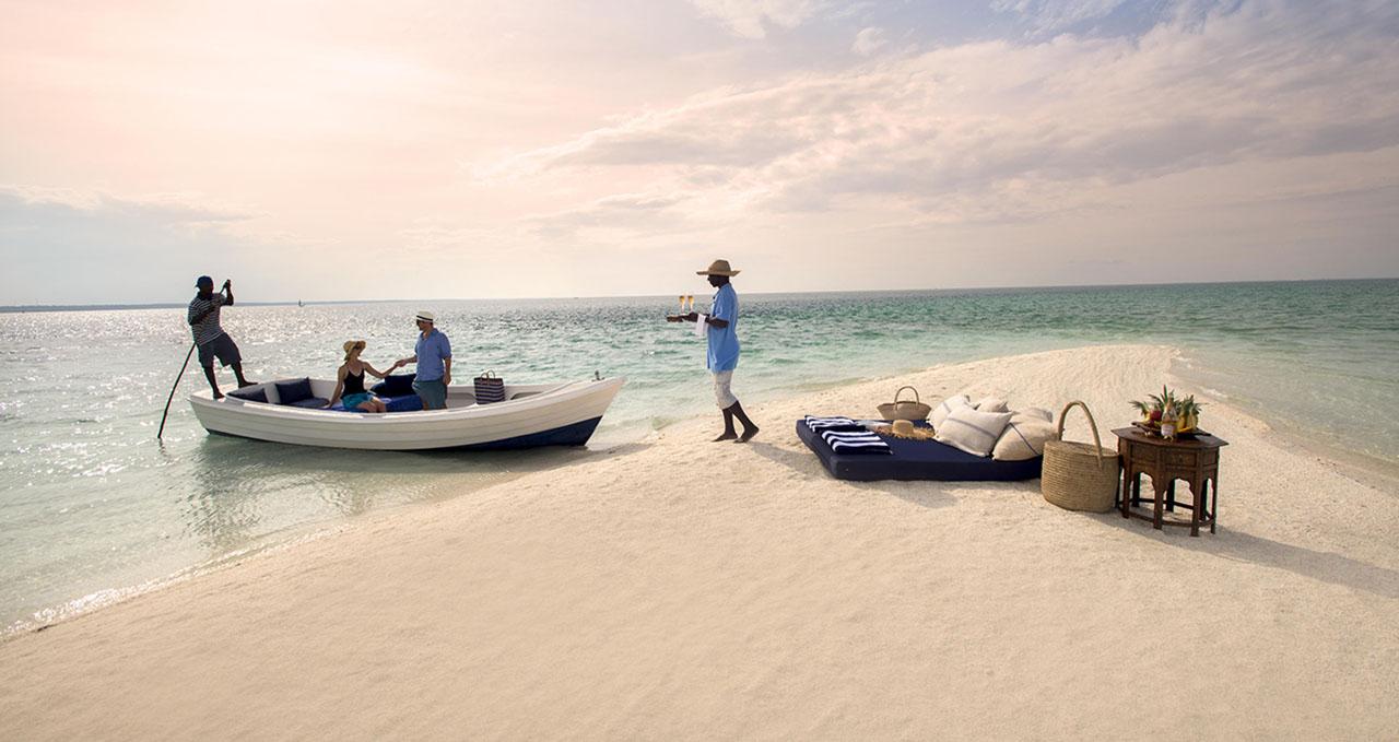 Mozambique, un couple arrive en bateau sur une île où les attend un serveur avec des rafraîchissements
