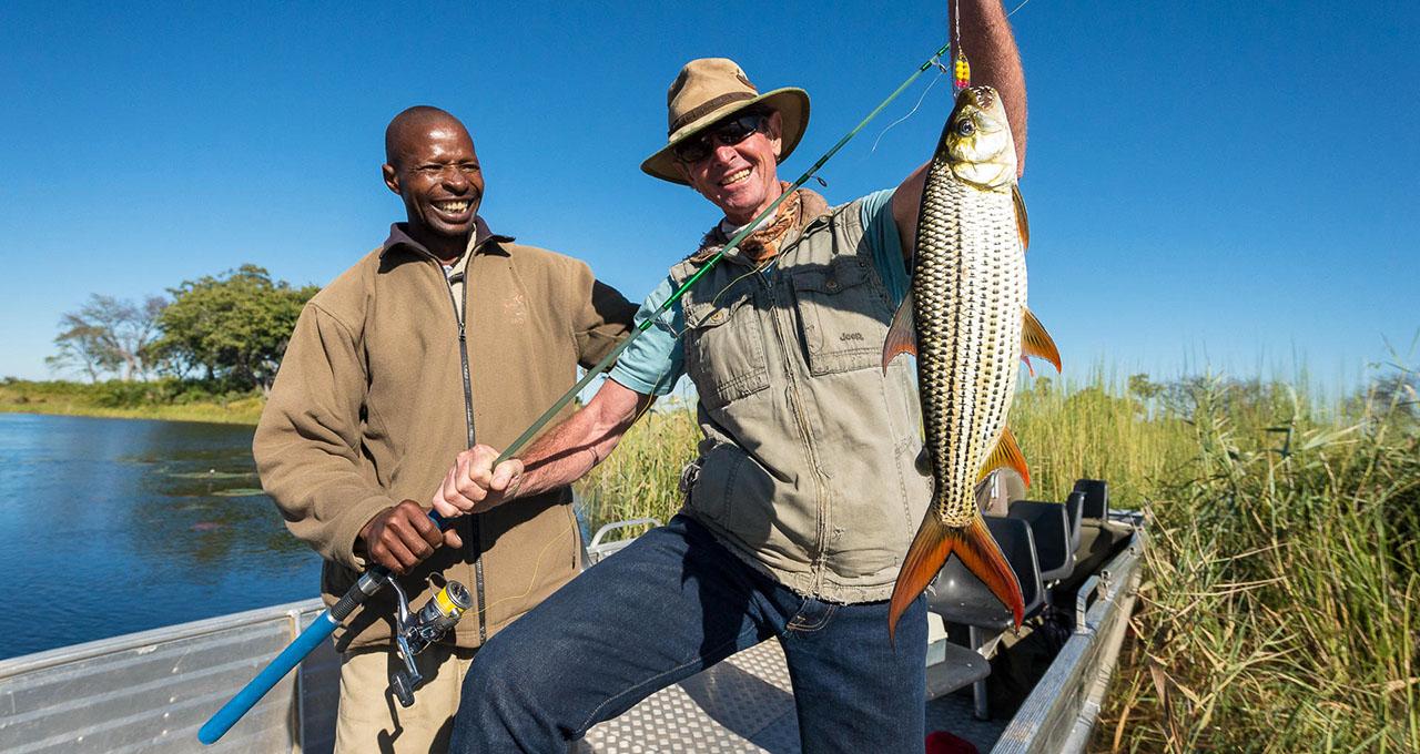 Botswana, un pêcheur en bateau accompagné de son guide présente avec fièreté sa prise, un poisson tigre