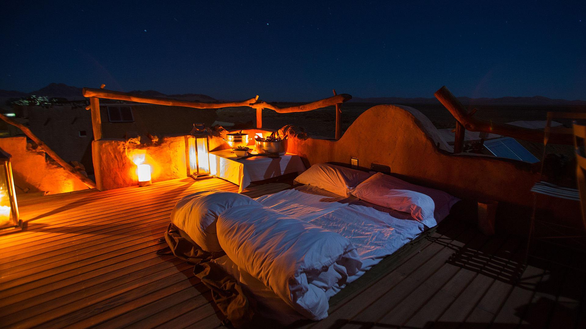 Namibie, désert du Namib : un lit est préparé dans une ambiance romantique sur le toit terrasse de la chambre pour une nuit à la belle étoile