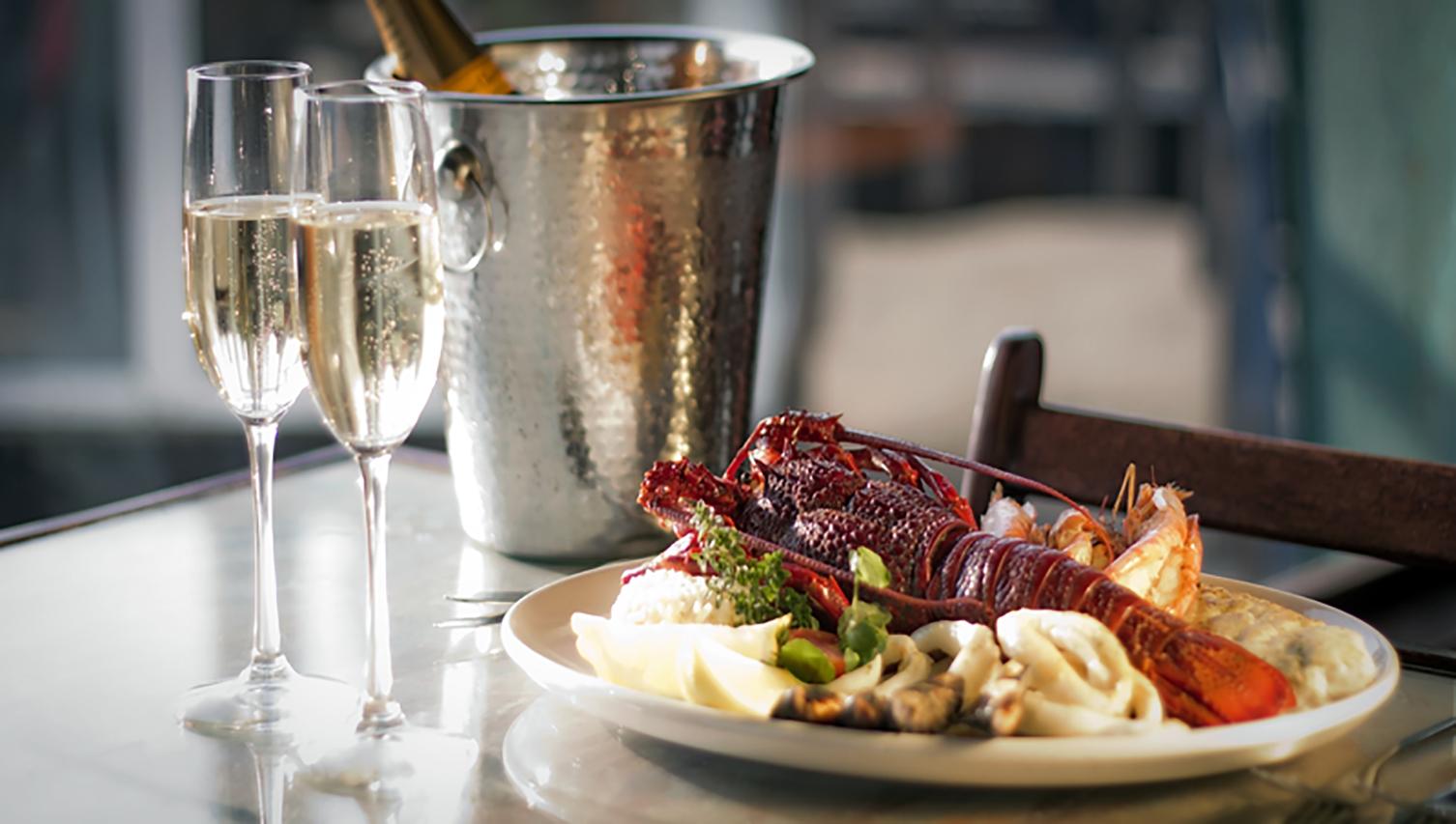 Namibie, repas culinaire : langouste dans une assiette dressée accompagnée de verres de vin pétillant