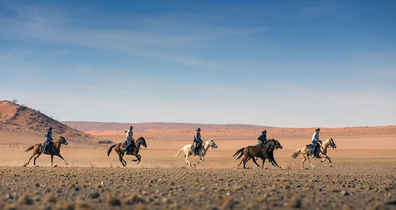 Namibie, un groupe de cavaliers galope parmi les dunes du désert du Namib