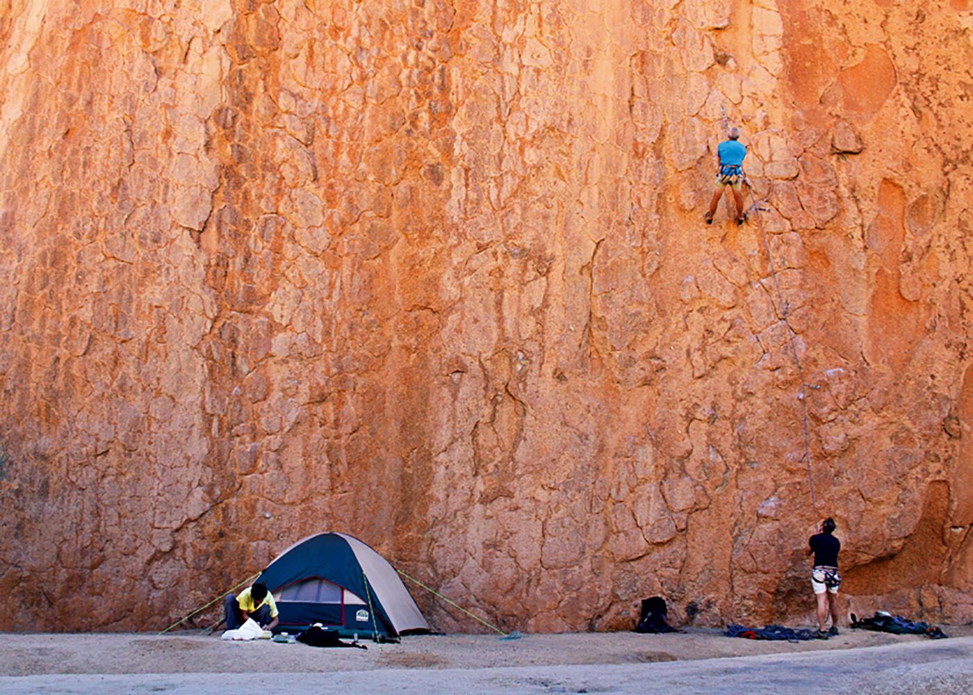 Namibie, une personne escalade une paroie de granite, assurée par une autre, leur tente à proximité.