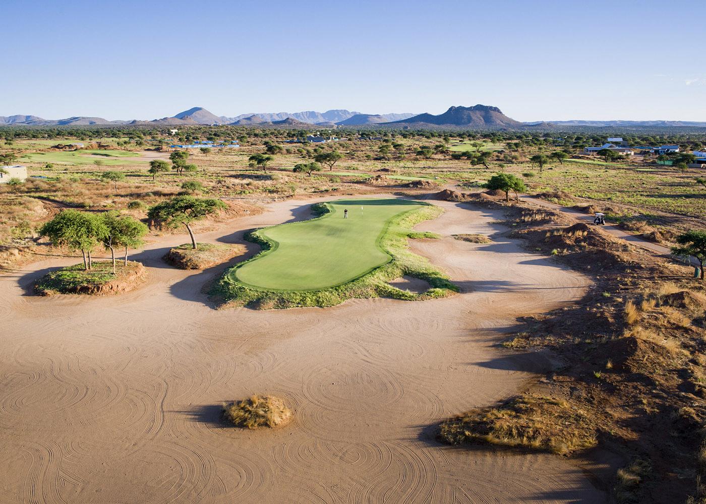 Namibie, à proximité de Windhoek, sur un parcours très vert, un golfeur à l'intérieur d'un bunker effectue un swing