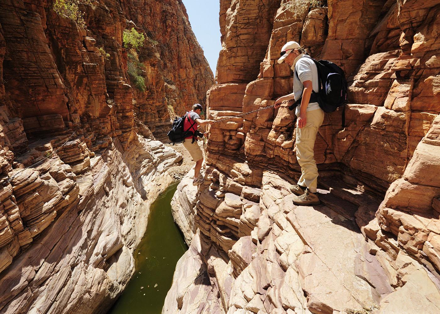 Namibie, Namib-Naukluft National Park, un couple traversant une gorge étroite de l'Olive Trail par une chaîne surplombant un bassin d'eau