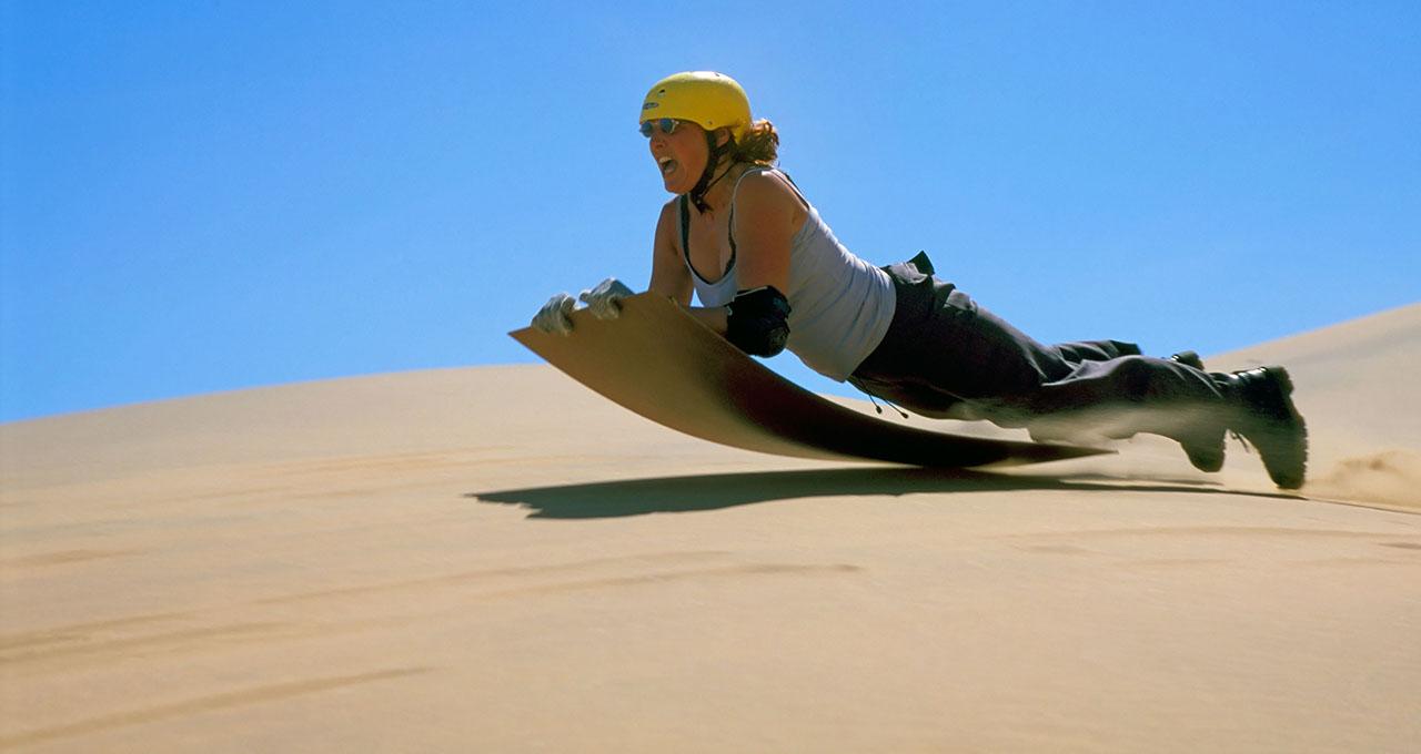 Namibie, la côte, femme sur sa planche hurlant de joie en descendant les dunes avec sa planche