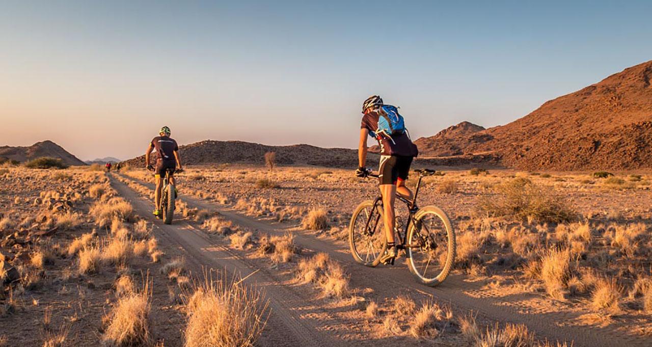 Namibie, cyclistes sur leur VTT suivent leur groupe parmi les reliefs et les paysages arides du Damaraland