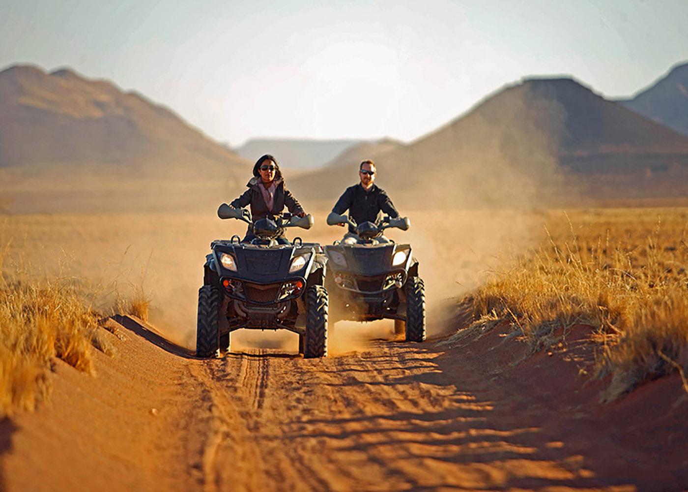 Namibie, désert du Namib, panorama de reliefs désertiques, deux personnes arrivent avec leur quad sur une chemin de sable