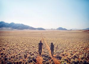 Namibie, Vue arrière d'un homme et d'une femme marchant sur une piste de chemin de sable 4x4 dans la réserve du Namibrand Nature Reserve