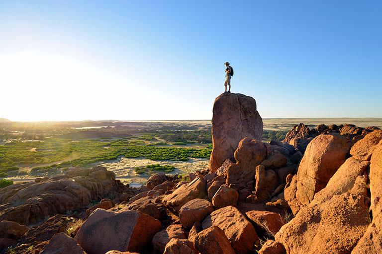 Namibie, Damaraland, randonneur perchée sur un rocher dominant la vallée de l'Ugab